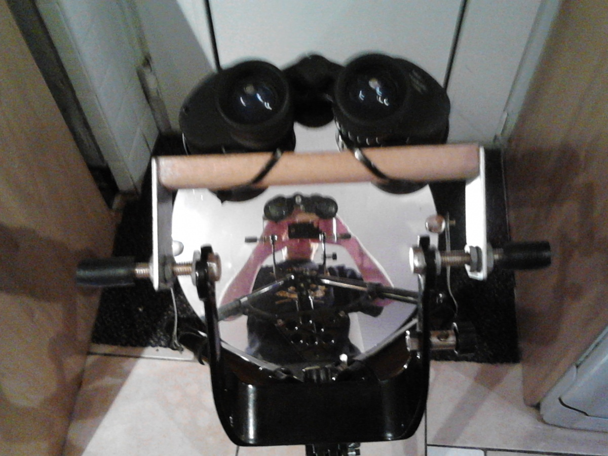 bino mounted on yoke of telescope stand. can swing left and right, my reflection in mirror taking shot.